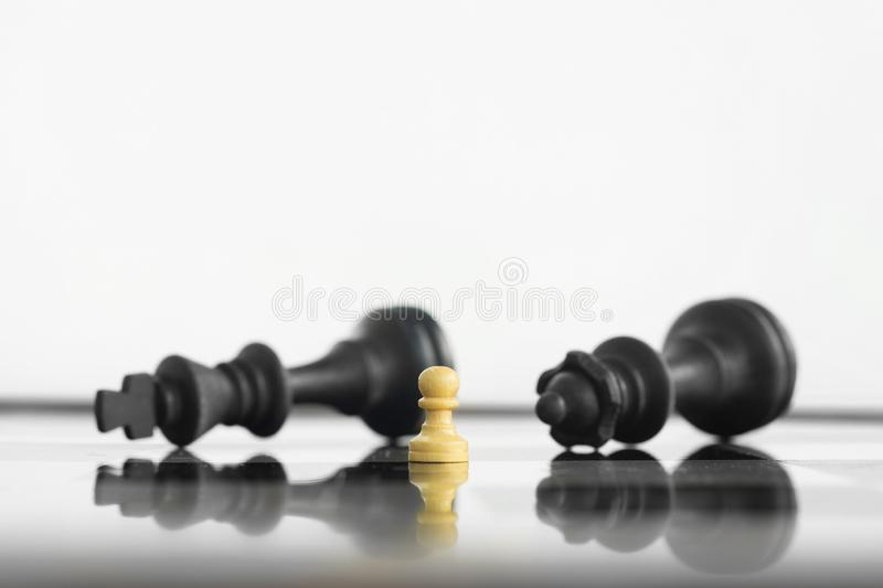 White peon standing victorious in front of a defeated King and Queen black chess army after confrontation royalty free stock image