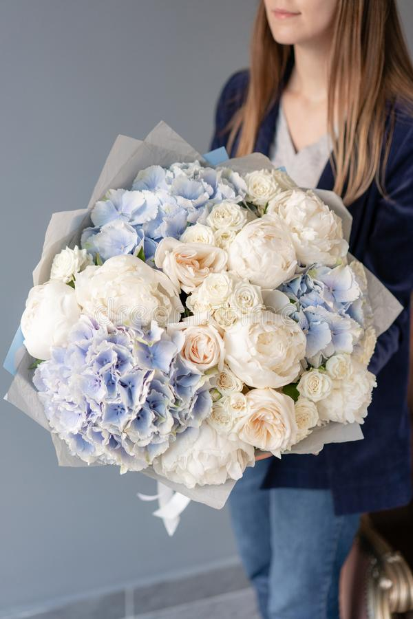 White peonies and blue hydrangea. Beautiful bouquet of mixed flowers in woman hand. Floral shop concept . Handsome fresh royalty free stock images