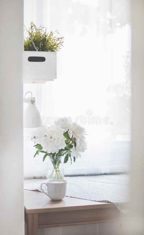 White Peonies in Clear Glass Vase Centerpiece Near a White Ceramic Mug Closeup Photography stock image