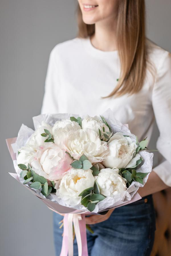 White peonies with eucalyptus in womans hand. Beautiful peony flower for catalog or online store. Beautiful bouquet royalty free stock photography