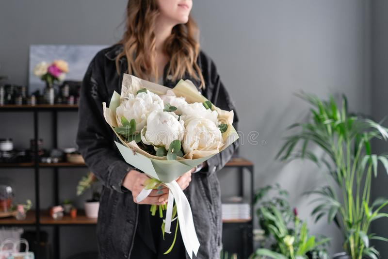 White peonies in womans hands. Beautiful fresh peony flower for catalog or online store. Floral shop concept. Flowers stock image