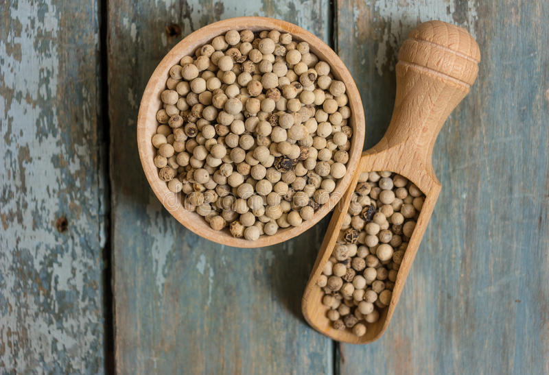 White pepper. Beans in a wooden bowl on a blue background stock image