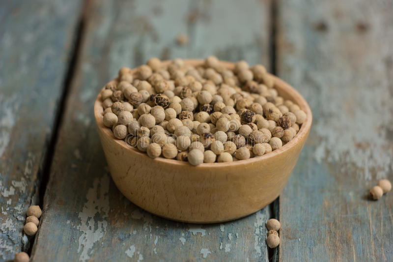 White pepper. Beans in a wooden bowl on a blue background stock photos