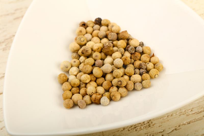 White pepper corn. Heap over wooden background stock images