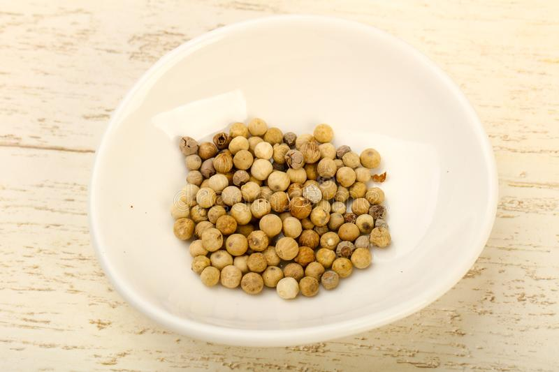 White pepper corn. Heap over wooden background royalty free stock images
