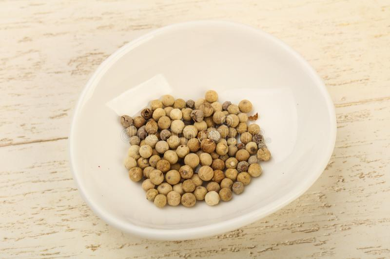 White pepper corn. Heap over wooden background stock image