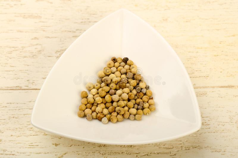 White pepper corn. Heap over wooden background royalty free stock image