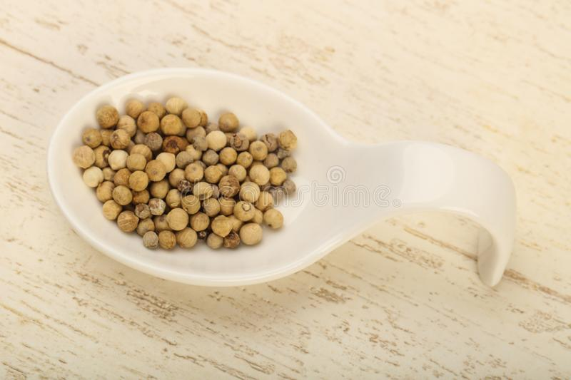White pepper corn. Heap over wooden background stock photos