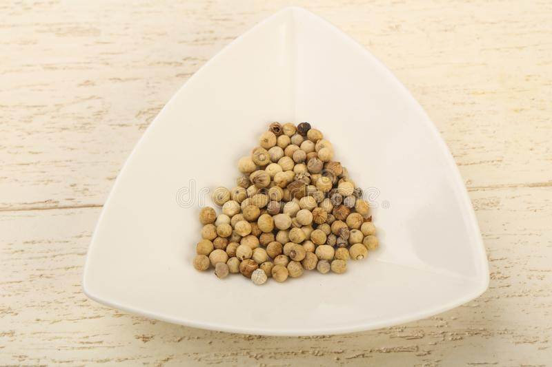 White pepper corn. Heap over wooden background royalty free stock photos