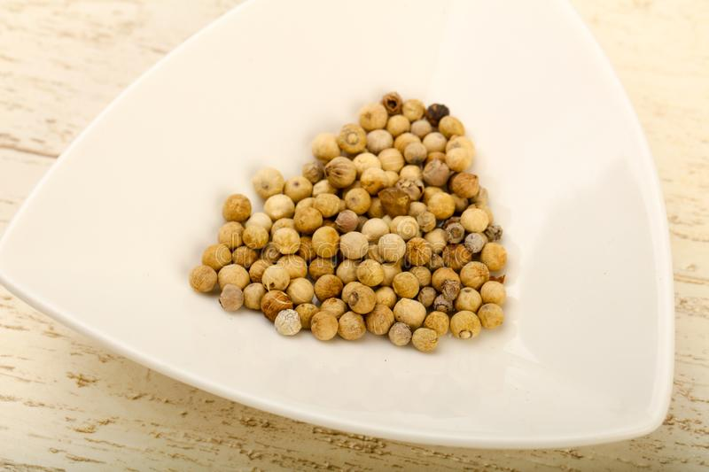 White pepper corn. Heap over wooden background stock photo