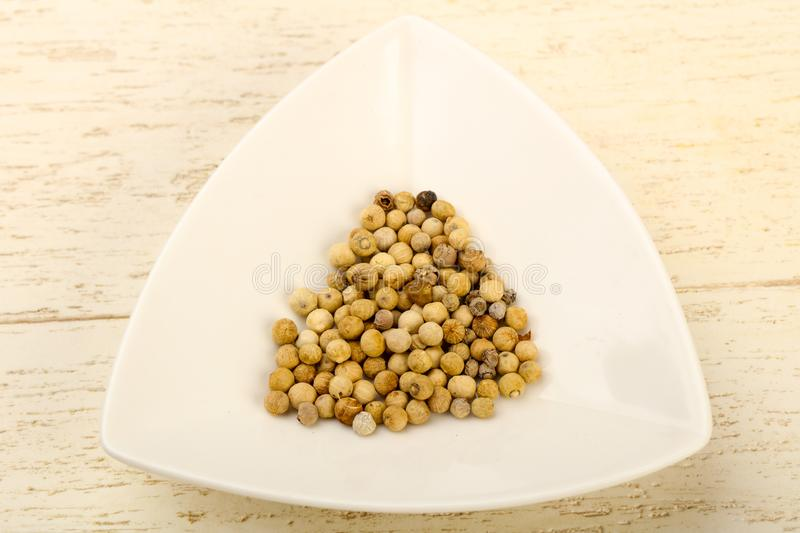 White pepper corn. Heap over wooden background stock photography