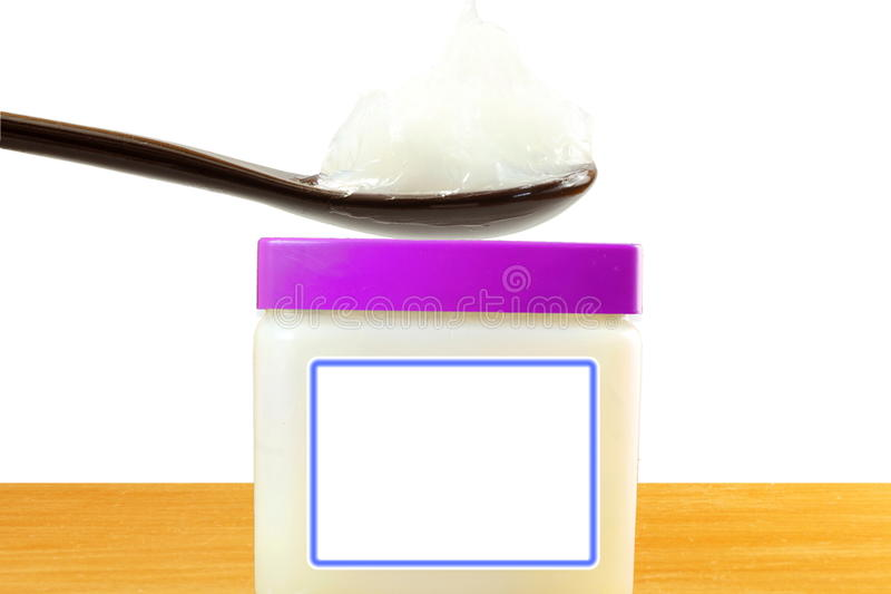 White petroleum jelly in spoon with jar in white background stock photo
