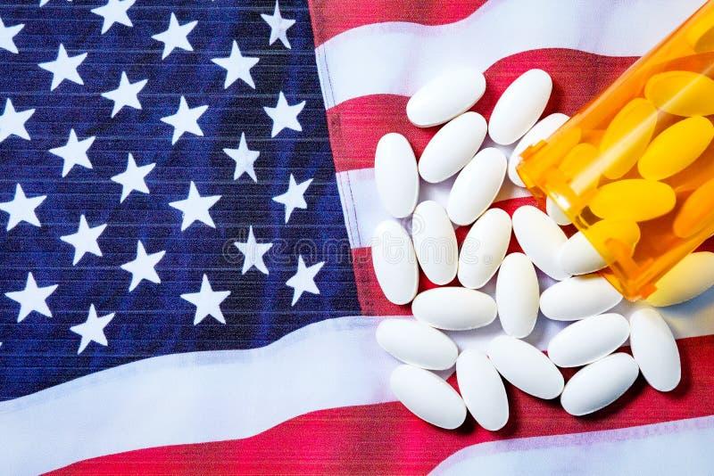 White pharmaceutical pills spilling from prescription bottle over American flag royalty free stock photography