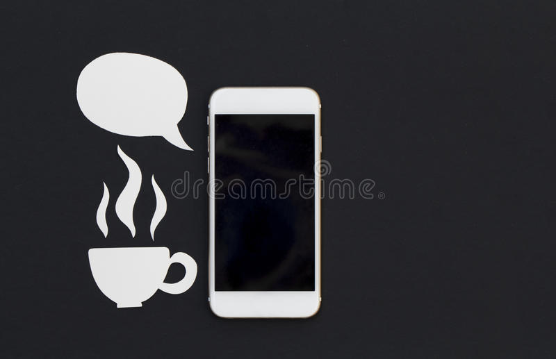 White phone and cartoon text bubble and hot drink cup. Breakfast with smartphone flat lay photo. Speaking cellphone banner template with text place. Black royalty free stock photography