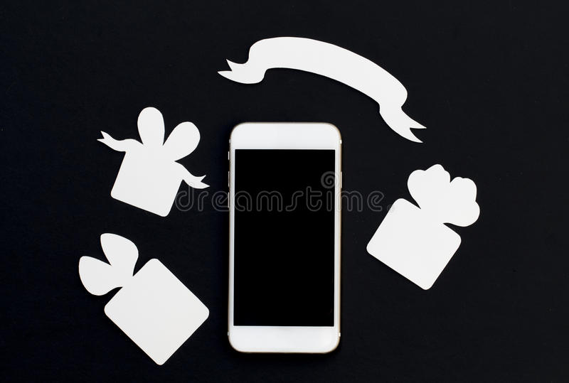 White phone with gift boxes and blank ribbon banner on black background. Black and white smartphone and paper cut presents. Black screen cellphone flat lay stock images