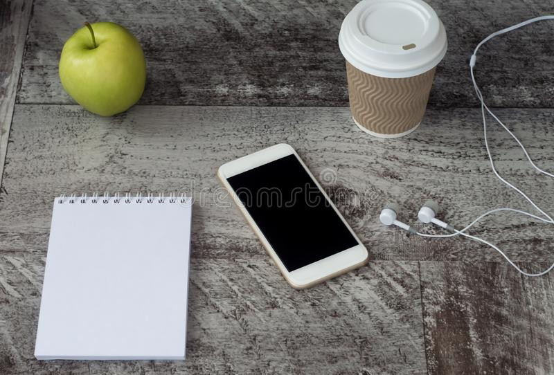White phone with headphones, coffee, notepad and green apple on the table. Work at home. Freelance.  royalty free stock photo