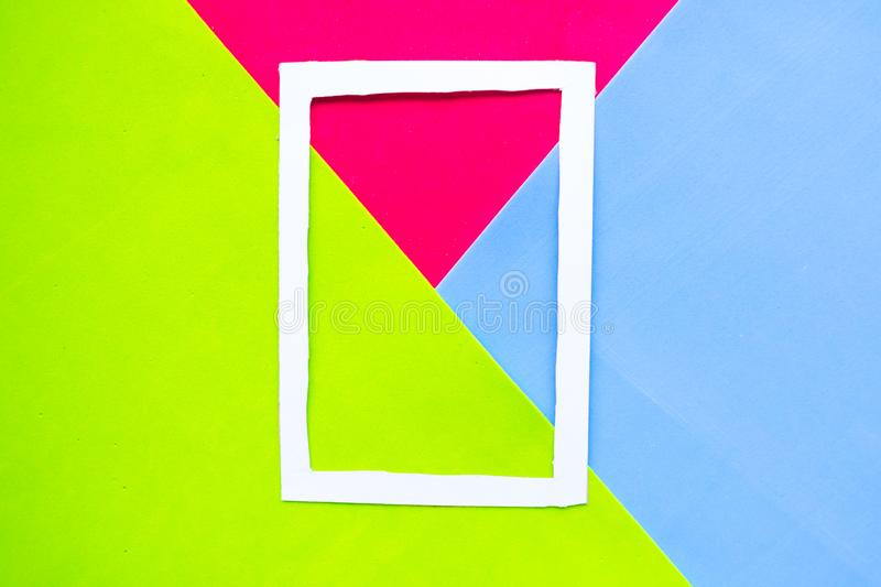 White photo frame on geometric green, blue and red paper background. Minimal concept stock photo