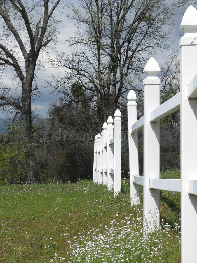 White picket fence in flowering meadow stock images