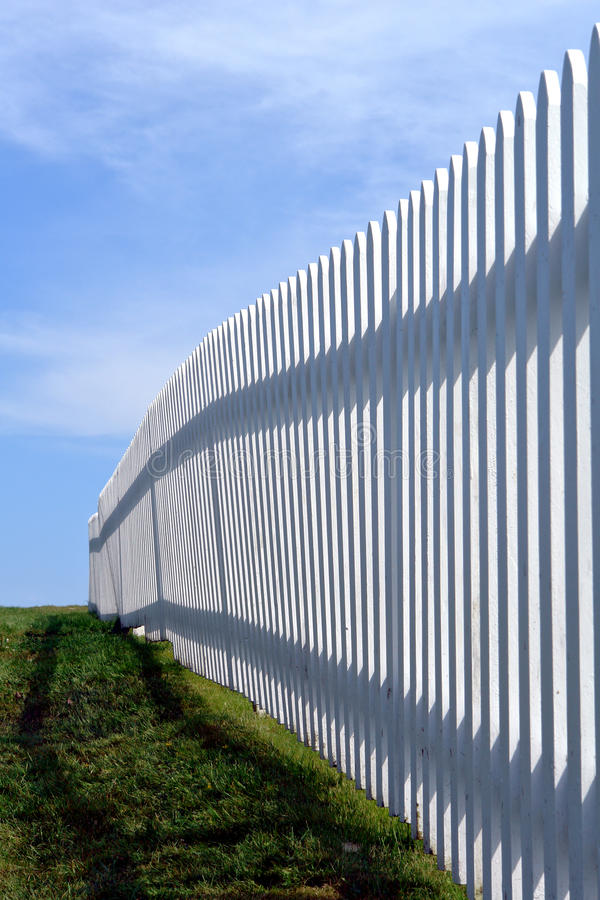 White Picket Fence in Green Grass over Blue Sky stock photography