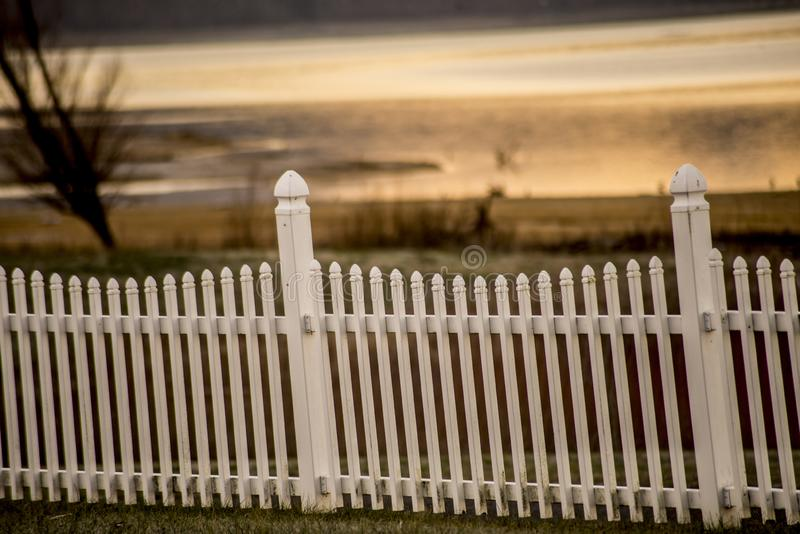 A white picket fence at sunset. stock photo