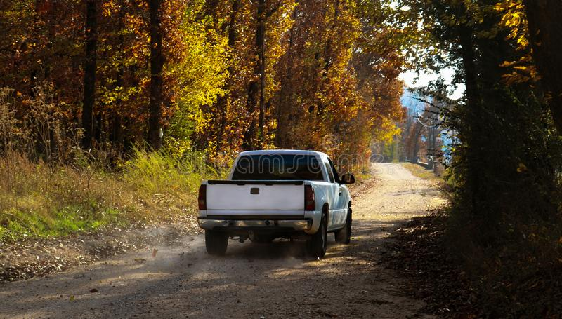 White pickup truck driving down dusty dirt road with fall leaves and dust behind royalty free stock photo