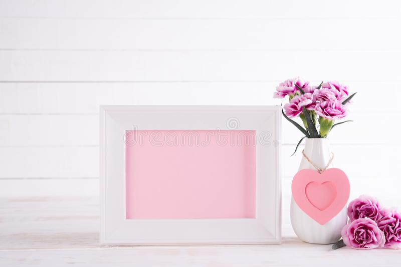 White picture frame with lovely pink carnation flower in vase on white wooden table stock photography