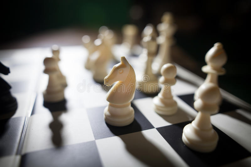 White pieces on chess board, focus on knight. Image of the white pieces on a chess board, with shallow depth of field and focus on the knight royalty free stock photos
