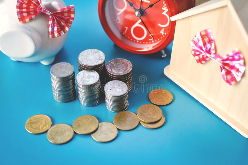 White piggy bank and alarm clock with wood house on table. Concept save money ,selective and soft focus royalty free stock photos