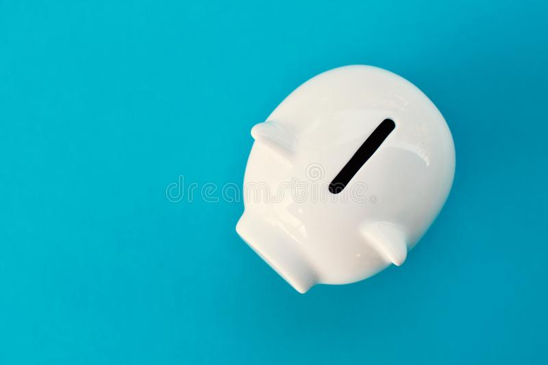 White piggy bank on blue background. Concept save money stock photo