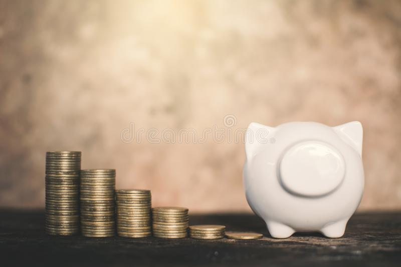 White piggy bank and coin on wood. Concept save money royalty free stock photography