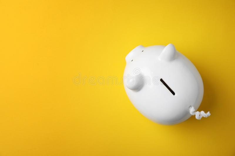 White piggy bank on color background. Top view stock photo