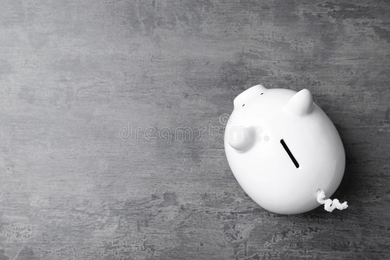 White piggy bank on gray table royalty free stock image