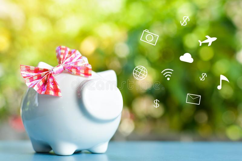 White piggy bank with icon on blue table. And tree bokeh background concept save money royalty free stock photography