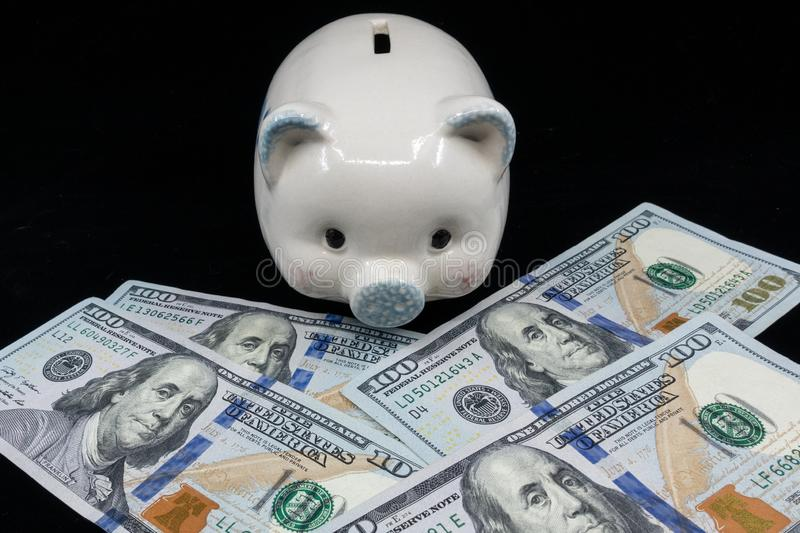 White piggy bank isolated close-up on a pile of United States currency against a black background. Wealth and savings concept. royalty free stock photography