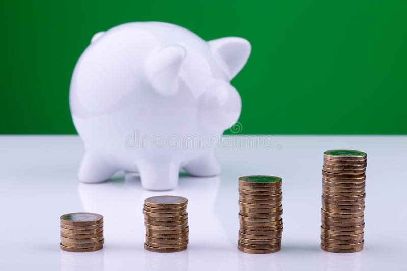 White piggy bank with stack of coins. White piggy bank with a stack of coins and a green background royalty free stock photos
