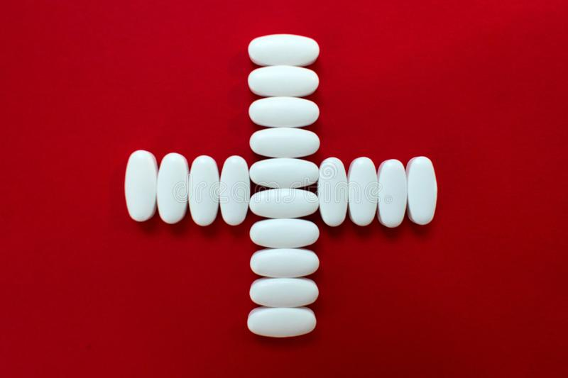 White pill cross on red background royalty free stock images