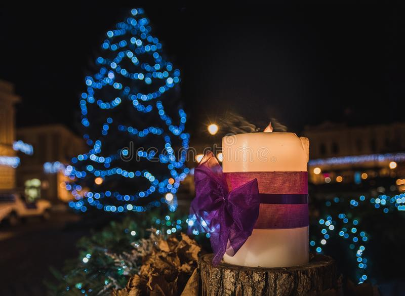 White Pillar Candle on the Log in a Distance of Blue Led Light Christmas Tree stock image
