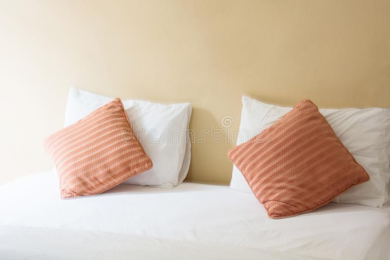 white pillow and orange pillow on bed and with blanket in vintage bedroom stock photos