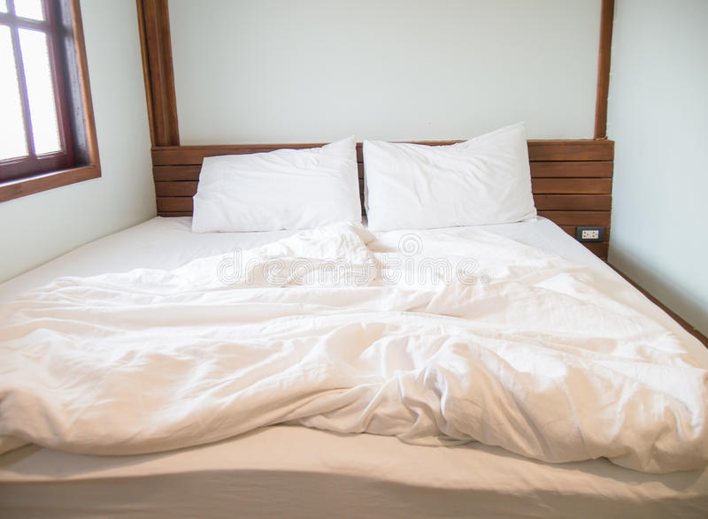 White pillows on the bed and a messy blanket in the bedroom royalty free stock image