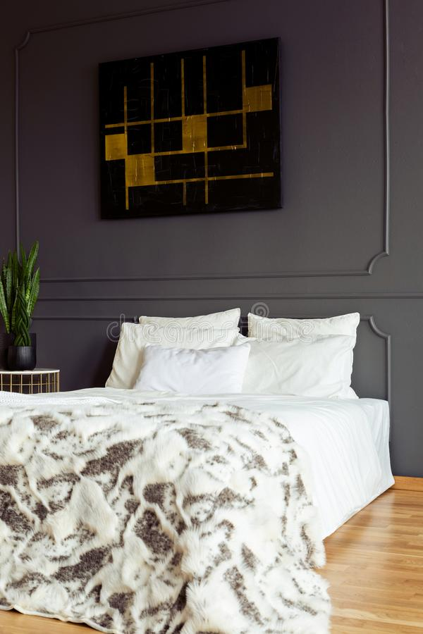 White pillows and blanket on a double bed in a grey bedroom interior with a black and golden painting. Real photo. Concept stock image