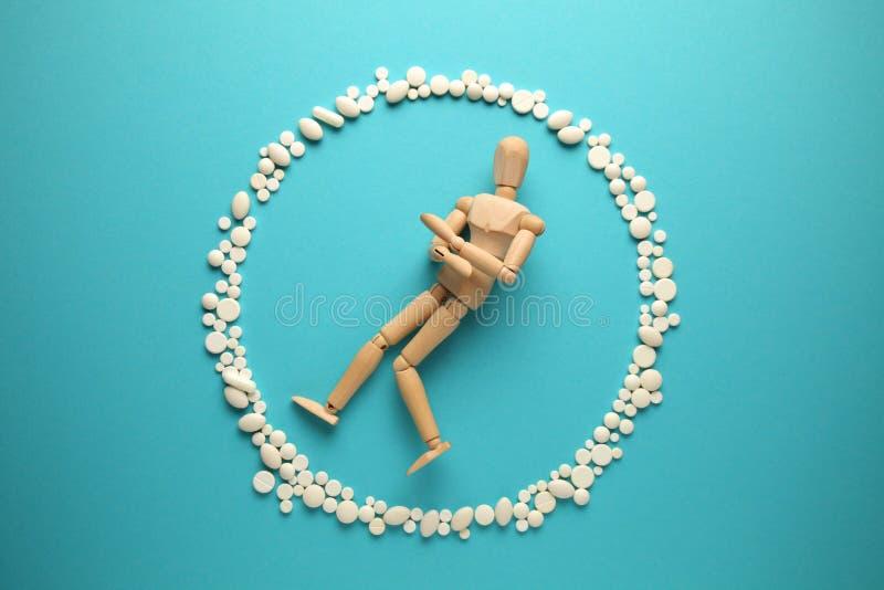 White pills around human figure. Abuse of antibiotics, dependence on drugs and painkillers.  stock image