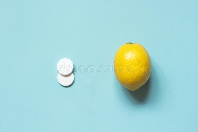 White pills and lemon on a blue background. The choice of treatment with medicines or folk remedies. Flu, colds. White pills and lemon on a blue background. The royalty free stock image