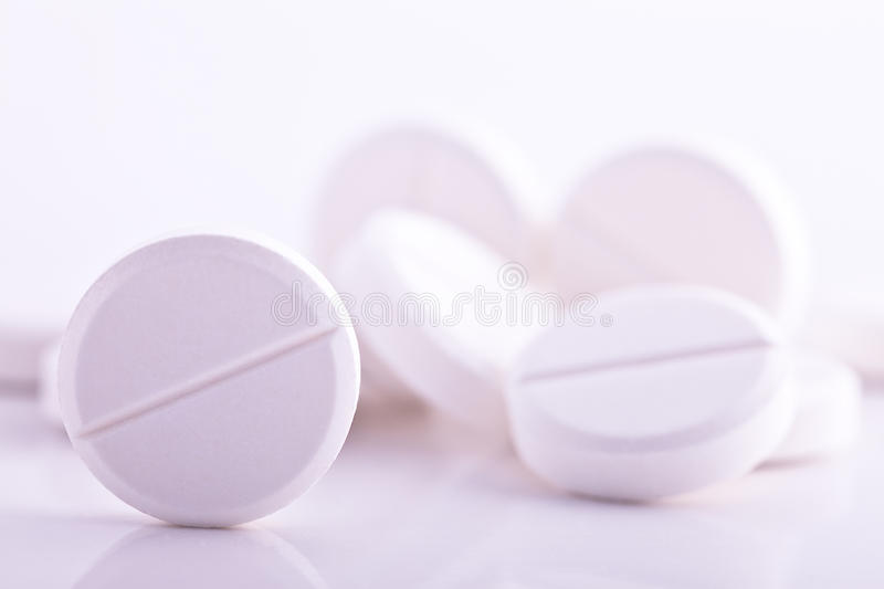 White pills medicine headache aspirin paracetamol. White pills on white background medicine to cure headache and other pain medicament to take care of diseases royalty free stock photography