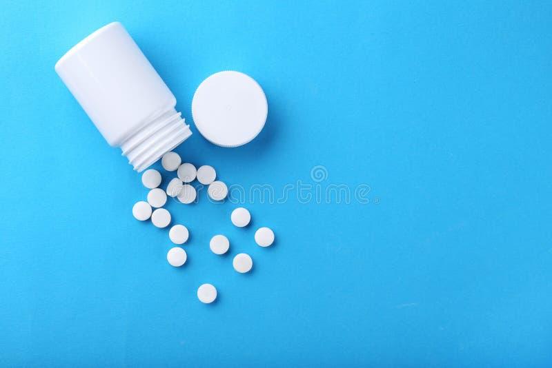 White pills. In plastic bottle on blue background stock image