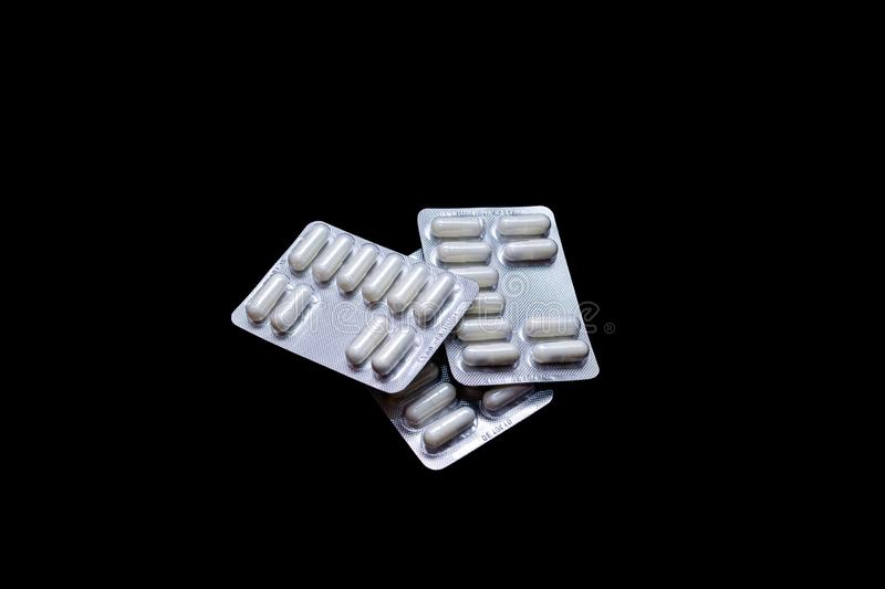 White pills in silver packs on a black background, isolate, copy space royalty free stock photos
