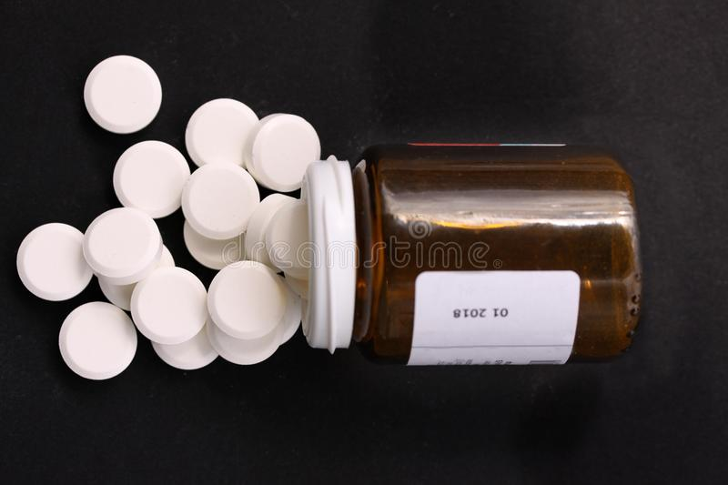 White pills spilled from fallen pill bottle. Pills and medicine container lying on black background illustrating drug addiction. T royalty free stock images