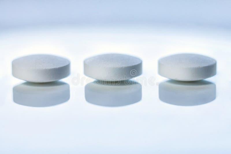 White pills. Three white round pills on the mirror surface stock image