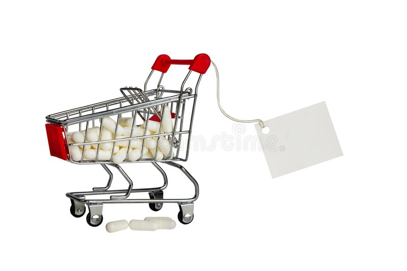 Little shopping cart full of pills with a price tag. Isolated. White pills in a toy shop cart. Isolate royalty free stock photo