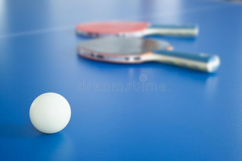 White ping-pong ball with rackets on background stock photos