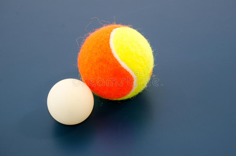 White ping pong ball and tennis ball. 40mm large white ping pong (table tennis) ball and tennis ball with blue background (raw file was provided stock photo